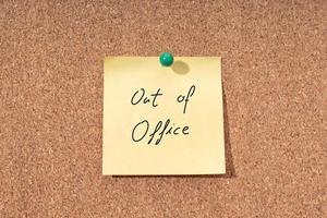 Nota amarilla con frase fuera de la oficina en tablero de corcho foto