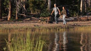 coppia con lo zaino in spalla lungo la riva del lago video