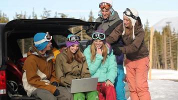 Grupo de jóvenes practicantes de snowboard en las pistas con portátil video