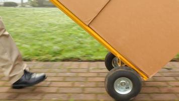 bezorger duwt dolly vol pakketten naar huis video