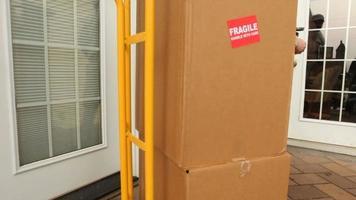 man bezorgt pakketten aan vrouw thuis video