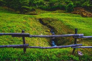 Meadow stream and wooden fence photo