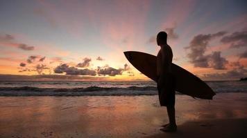 Surfista caminando por la playa al amanecer, Hawaii video