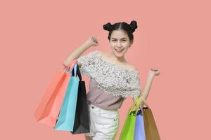 Attractive shopper woman holding shopping bags on salmon background photo