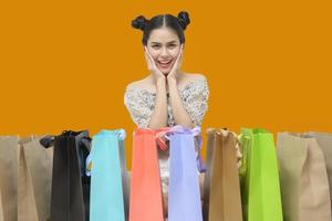 Attractive shopper woman holding shopping bags on yellow background photo