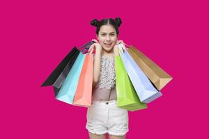 Attractive shopper woman holding shopping bags on pink background photo