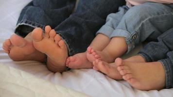 Gros plan des pieds nus de la famille au lit video