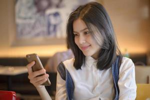 Attractive woman checking her messages on smartphone while sitting on coffee shop photo