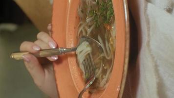 video verticale bella donna bionda che mangia e beve in pausa pranzo al ristorante