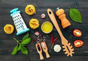 La pasta sobre fondo de madera negra.pasta italiana amarilla con ingredientes comida italiana y concepto de menú. foto