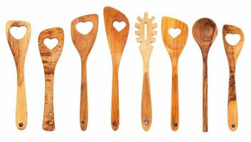 Varios en forma de corazón de utensilios de cocina de madera cucharas de madera y espátula de madera aislar sobre fondo blanco. foto