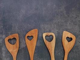 Varias en forma de corazón de utensilios de cocina de madera cucharas de madera y espátula de madera sobre fondo de hormigón con espacio plano y copia foto