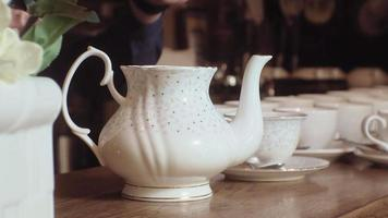 A man pours tea from a kettle into a white cup on a wooden table video