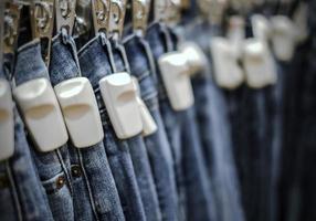 Etiqueta dura RFID en pantalones vaqueros azules en la tienda foto