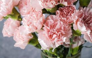 flores de clavel rosa en florero de vidrio foto