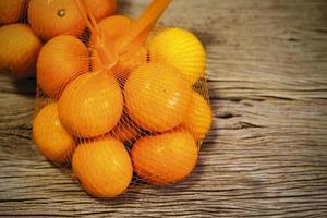 Mandarina en paquete sobre fondo de madera con espacio de copia foto