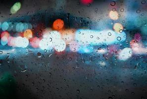 Raindrops with light bokeh on the road rain season background photo