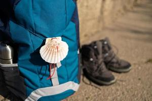 Close-up of a seashell, symbol of Camino de Santiago on backpack and trekking boots photo