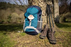 Backpack with seashell, symbol of Camino de Santiago with trekking boots and poles photo