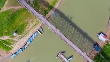 Aerial top view of Wooden bridge with tour boat in Thailand photo