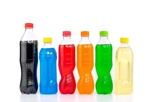 Multi colored drinks in plastic bottles isolated on white background photo