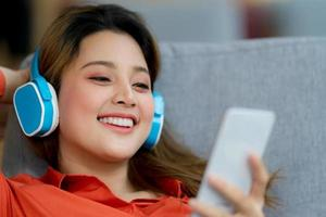 Portrait of young beautiful woman enjoying the music with smiley face sitting in creative office or cafe photo