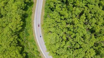 Aerial top view car driving through the forest on country road photo