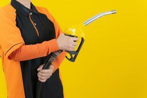 Mujer mantenga boquilla de combustible sobre fondo amarillo foto