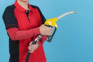 Mujer mantenga boquilla de combustible sobre fondo azul. foto