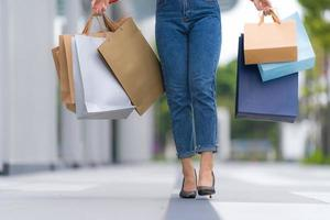Outdoors portrait of Woman leg with holding shopping bags photo
