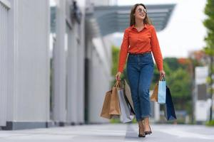 Outdoors portrait of Happy woman holding shopping bags photo