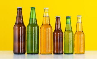 Six bottles of beer on a yellow background photo