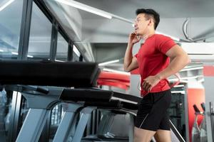 Athletic young man running and listening to music from his smartphone in gym photo