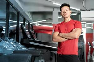 Athletic young man standing with arms crossed in gym photo