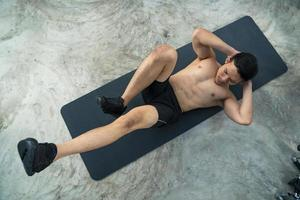 Sporty man training doing exercise in fitness gym photo
