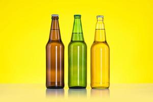 Group of Three bottles of beer isolated on yellow background photo