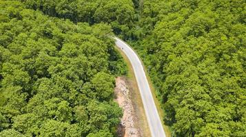 Aerial top view of a provincial road passing through a forest background photo