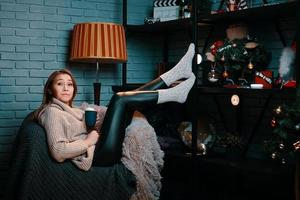 Woman with cup of cocoa sitting on chair photo