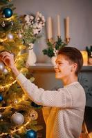 Smiling guy decorating Christmas tree photo