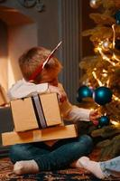 Little boy is sitting near Christmas tree with present boxes photo