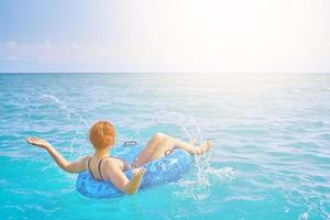 Redhaired girl splashes water in the swimming circle photo