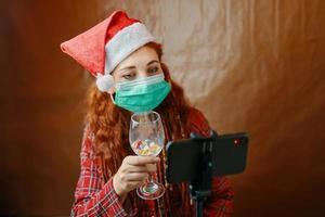 Woman with medical mask make Christmas video call photo