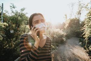 Young woman using a face mask making a call in a garden photo