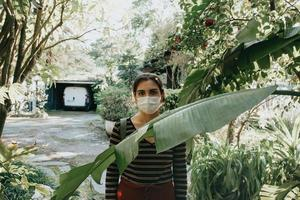 Woman using a mask standing in a garden looking at camera photo