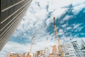 Bunch of yellow cranes under a bright blue sky with copy space photo