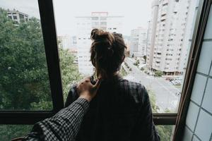 Person holding a woman near window photo