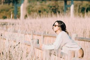 Mujer con gafas de sol en el patio del país mirando a otro lado foto
