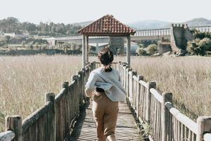 Mujer huyendo por un camino de madera en medio del campamento. foto