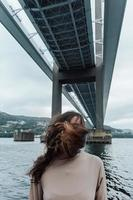 Portrait of a woman with moving hair under a bridge photo