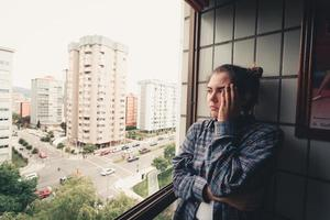 Worried woman looking from the window of her flat photo